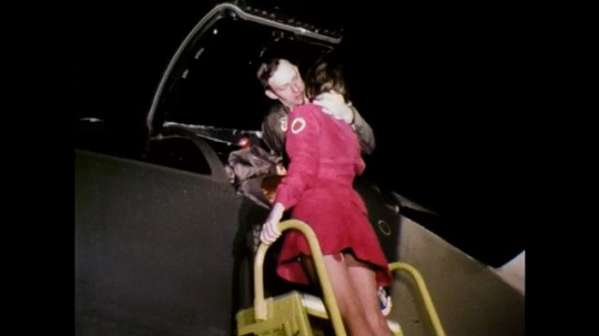 1970s: Bomber kisses woman on ladder off aircraft, woman descends, bomber holds flashlight and talks, dismounts, second bomber douses him with champagne.