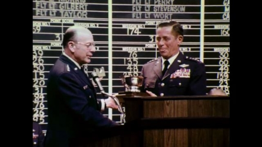 1970s: Two men in uniform exchange trophy in front of scoreboard at podium on stage, shake hands.