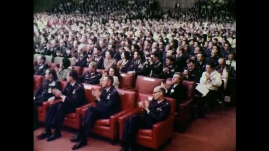 1970s: Audience clapping, seated. Line of men in uniform receive trophies at microphone as photographers take photographs below stage.