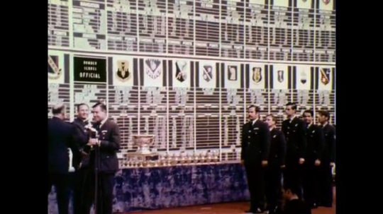 1970s: Men lined up on stage to receive trophies, one receives trophy and turns. Trophy details. Trophy on stand. Men in uniform walk down aisle in line.