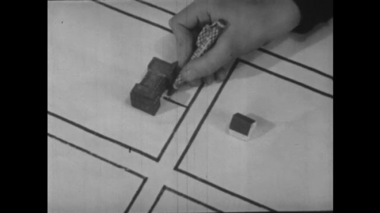 1940s: Hand draws a line on map from model of school to street. Pine Street is written on the map and a line is drawn down the street.