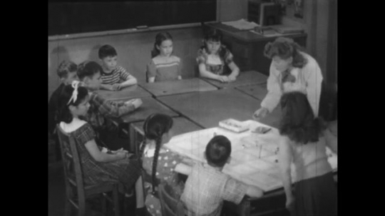 1940s: Teacher and students look at map on table in classroom. Students raise hands. Teacher hands model to boy. Boy places model on map. Teacher hands crayon to boy. Boy points to map.