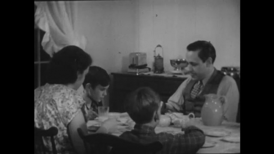 1940s: Family sits around dining table in home. Boy shows family piece of paper from pocket. Father reads it.