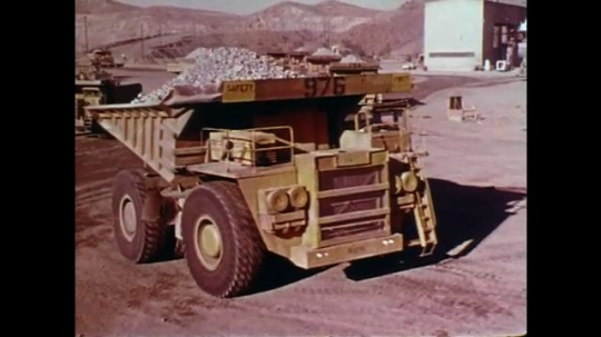 1970s: large mining vehicles drive through construction site