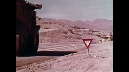 1970s: Two large trucks move toward each other. Loaded truck has right of way while other truck obeys yield sign