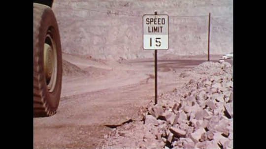 1970s: Truck slowly drives past a speed limit sign. Truck drives on slippery road