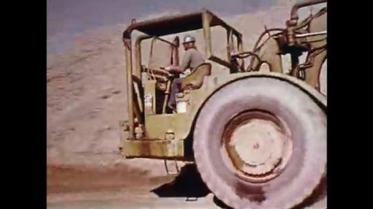 1970s: Man drives large tractor downhill. View of underneath vehicle. Construction worker repairs a large wheel.