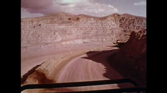 1970s: Truck moves slowly down hill, keeps distance from truck ahead. View of driver's foot pumping brake pedal. View of rpm on dashboard. Truck moves slowly over rocky terrain