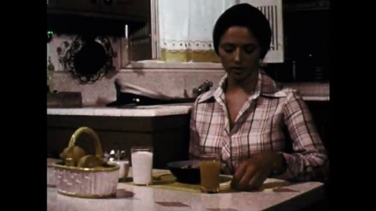 1970s: Young woman serves herself breakfast. Young woman eats breakfast.