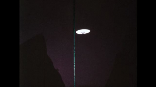 1970s: UFO flies away in the night sky. Person with shield and ray watches UFO fly away.