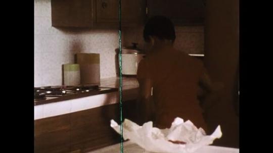 1970s: Boy places pan on stove. Boy puts patty in pan. Boy opens fridge. Boy takes mayonnaise. Boy takes bread.
