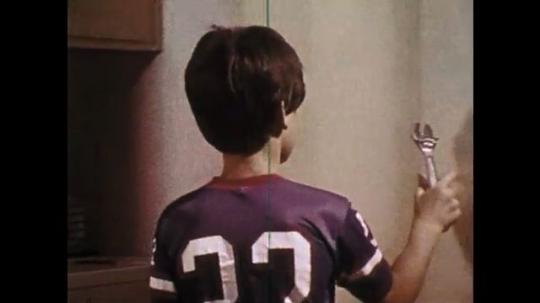 1970s: Boy puts tools away. Boy notices box. Boy finds gun. Boy picks up gun.