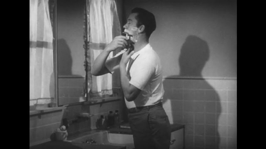 1950s: Lady speaks. Man shaves his face. Lady smiles. Lady walks into kitchen
