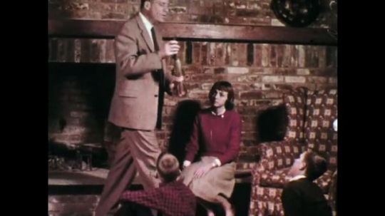 1960s: Man holds rocket model and sits down. Lady wears red jersey.  Man gestures to rocket and speaks. Kids sit on floor and watch man. Rocket flying upward in space