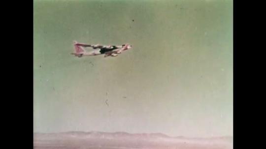 1960s: Plane flies in sky. Plane carries smaller jet. Plane moves forward in sky
