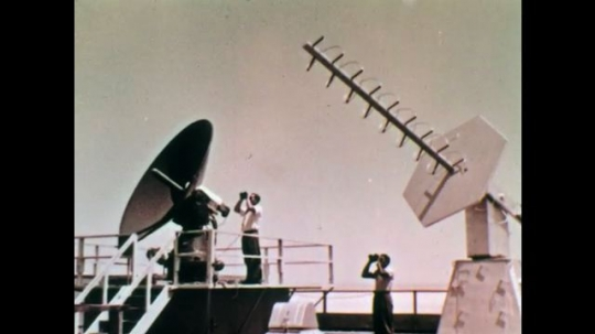 1960s:  Satellite and aerial point to the sky. Men stand next to satellite and aerial. Plane flies in sky. Plane carries smaller jet. Plane moves forward in sky