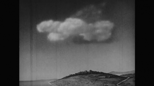 1950s: Animation of darkening cloud drifts over coastal landscape of hills and trees. Animation of dashed rainfall cascades from cloud.