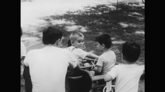 1950s: man rocks boys on seesaw toy as boy gets out, grabs and chases after child on tricycle at playground