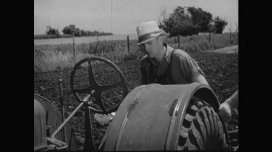 1930s: Boy climbs on tractor, pushes lever. Boy starts tractor, plows field.