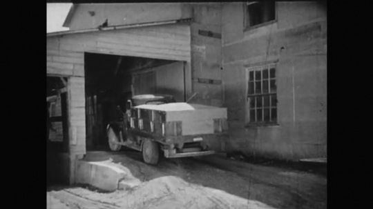 1930s: Truck pulls into grain elevator. Men open truck gate, grain pours out. Grain pouring. Hands pull dough from machine.