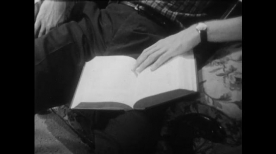 1950s: Man sleeps in chair with book open on lap. Woman walks into room, smiles at sleeping man.