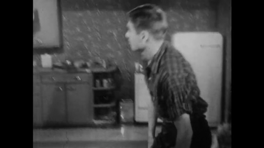 1950s: Man gets up from chair, holds woman