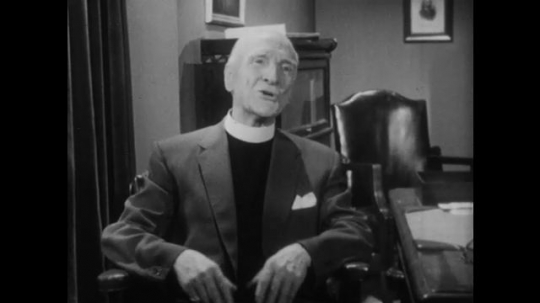 1950s: Priest sits in chair, talks. Man walks across room, sits on arm of chair next to woman.