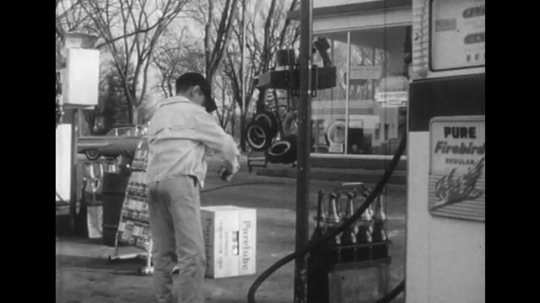 1950s: Boy puts item in pocket, walks from gas station. Boy enters house, pan to woman talking.