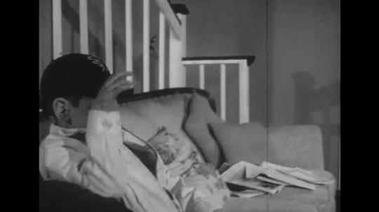 1950s: Boy sits on sofa, pulls down hat, woman sits, removes boy