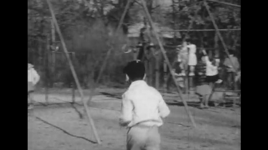 1950s: Boy runs toward other boys on playground. Woman on playground, helps girl reach ring.  Close up of woman.