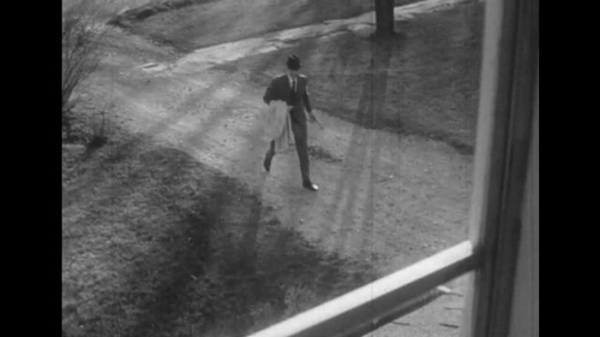 1950s: View through window, man approaches house. Boy in window. Man enters house, looks at mail.