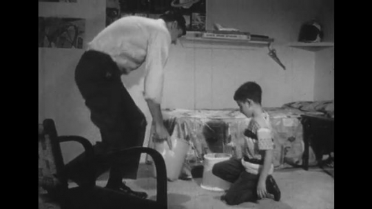 1950s: Man and boy sit on bed, man removes boy