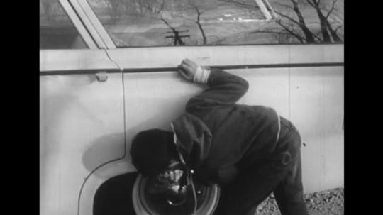 1950s: Tilt down, boy polishes car tire. Boy tries to pull up on bar, falls.