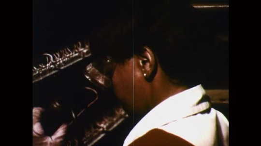 1970s: woman with goggles solders wires with iron, climbs ladder and inspects connections on telephone circuit boards.