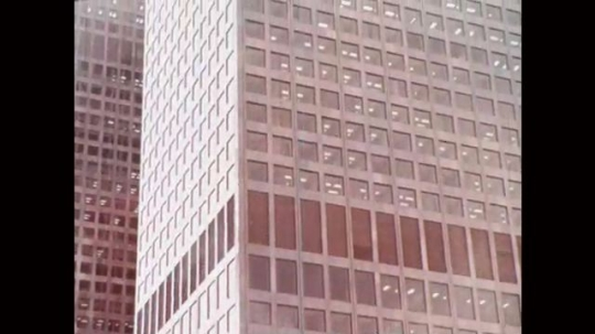 1970s: tall building in downtown. woman holds file and walks through office as women type and sort papers at desks. woman and man sit and talk at table in conference room.