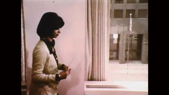 1970s: woman opens folder as man sits at desk and reads paperwork. woman talks on telephone and smiles. woman walks down sidewalk and pushes open glass door.