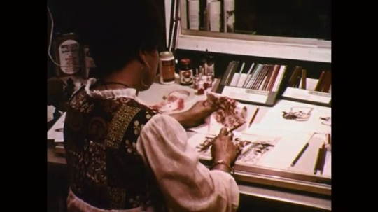 1970s: woman sits at drafting desk, draws on paper with various color pencils.