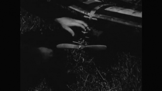 1950s: A young man starts the propeller on a model plane. Another man watches as he picks up the plane and throws it in the air. The plane flies in a straight line with clouds in the background.