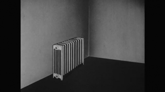 1950s: Radiator sits next to end table. Girl approaches radiator and opens hand. Feather drifts up, gently blown by radiator. She catches feather between two hands and repeats drifting the feather.