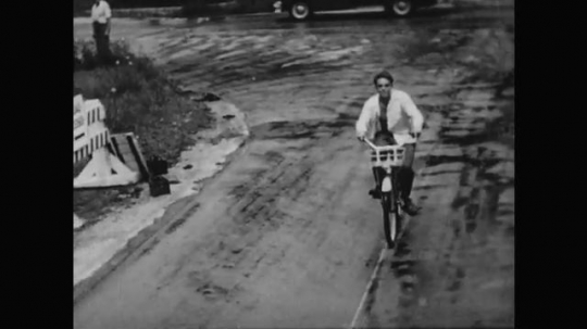 1950s: A young man with an open shirt leisurely rides his bike on a rain-soaked street. Young woman in dress steps off dock into sailboat with three other people.