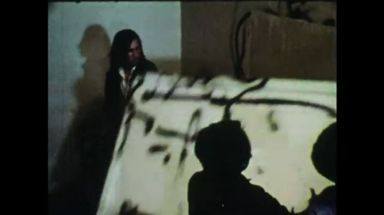 1970s: Teenagers vandalize and destroy things in a room. Guy sets paper on fire and puts it in flaming garbage can.