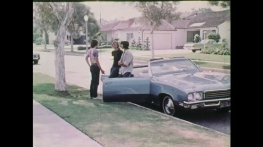 1970s: Teenagers stand around a parked car talking to each other.