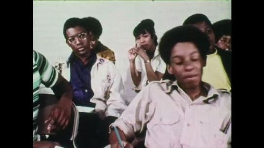 1970s: Teenage boy sits in a busy classroom by himself.