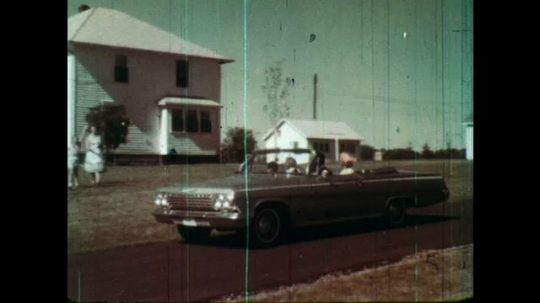1960s: convertible 1962 Chevy Biscayne or Impala drives up near house as woman and girl walk down and wave.