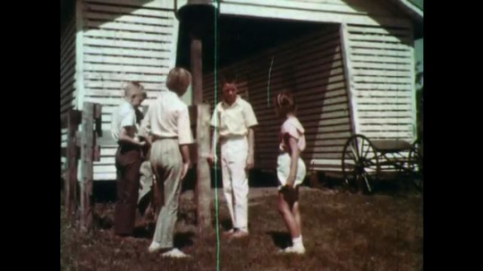 1960s: boys and girl stand near bell on post, talk and run off. man tugs cow udder near penned cows on milking machines as boys and girls arrive in dairy barn.
