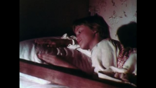1960s: girl pats down pillow and sleeps in dark room. sun shines into bedroom as girls wake up, stretch and talk on bunk beds.