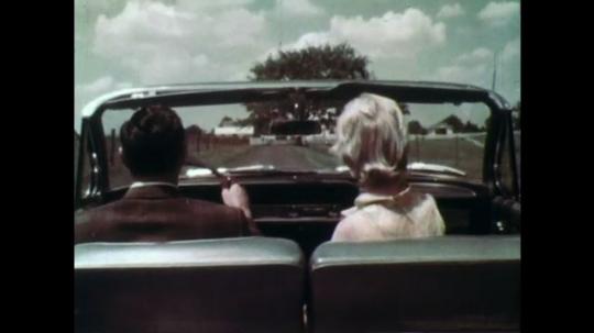 1960s: man and woman drive convertible 1962 Chevy Biscayne or Impala up dirt road to farm. boy and girl sit, wave and jump down from fence. man loads suitcases into trunk of car as men and women talk.