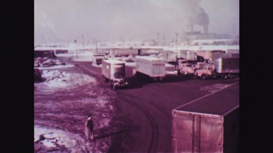 1950s: Trucks pull in and out of lot. Car waved into lot by attendant at entrance/exit. Car stops next to building. Man in uniform gets out, closes door. Woman in car slides into driver