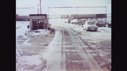 1950s: POV driving toward exit from snowy lot/yard. Stop sign. Driver in truck waves to attendants at exit. POV truck exits, turns past building marked Transportation Co., parked cars and trucks.