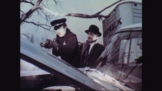 1950s: Man in uniform extinguishes engine fire while another man watches. Man with extinguisher sighs, speaks to second man. Second man responds. Man in uniform speaks.